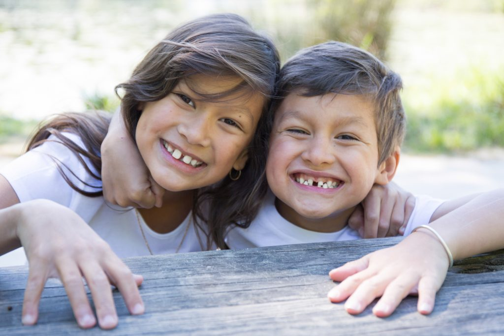 A photo of a smiling girl and boy